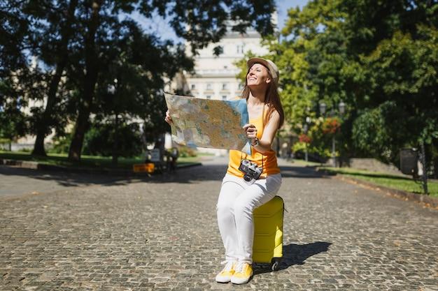 노란색 옷을 입은 행복한 여행자 관광 여성, 모자는 도시 야외에서 도시 지도 검색 경로를 들고 여행 가방에 앉아 있습니다. 주말 휴가를 여행하기 위해 해외로 여행하는 소녀. 관광 여행 라이프 스타일.