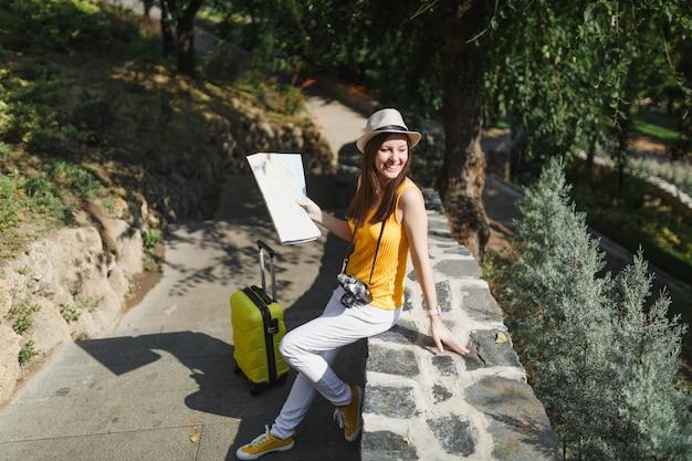 街の屋外の石の上に座って脇を探しているスーツケースの都市地図と黄色の服の帽子をかぶった幸せな旅行者の観光客の女性。週末の休暇で旅行するために海外旅行する女の子。観光の旅のライフスタイル。