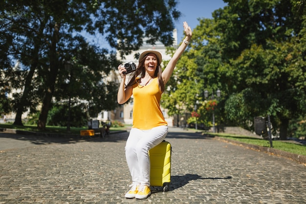 Happy traveler tourist woman sitting on suitcase hold retro vintage photo camera waving hand for greeting, meeting friends outdoor. girl traveling abroad on weekend getaway. tourism journey lifestyle.