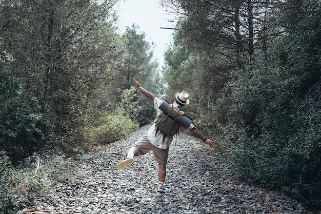 放棄された線路の小道を歩いている幸せな旅行者