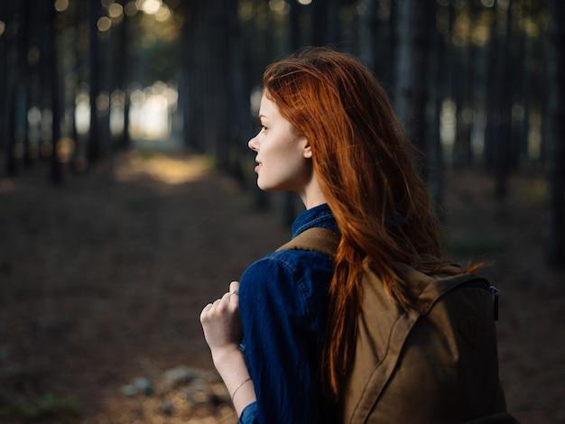 그녀의 등에 배낭을 든 행복한 여행자는 소나무 숲에서 자연 속에서 쉬고 있습니다.