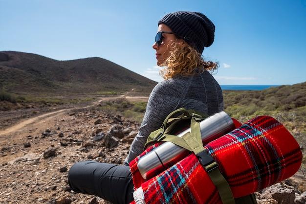 山の地面に座って渓谷の景色を楽しんでいるバックパックと水のボトルで幸せな旅行者。田園風景、アフリカへの旅行、幸福感、夏休みのコンセプト