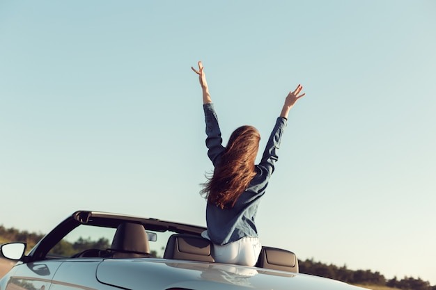 Happy traveler woman in cabrio car