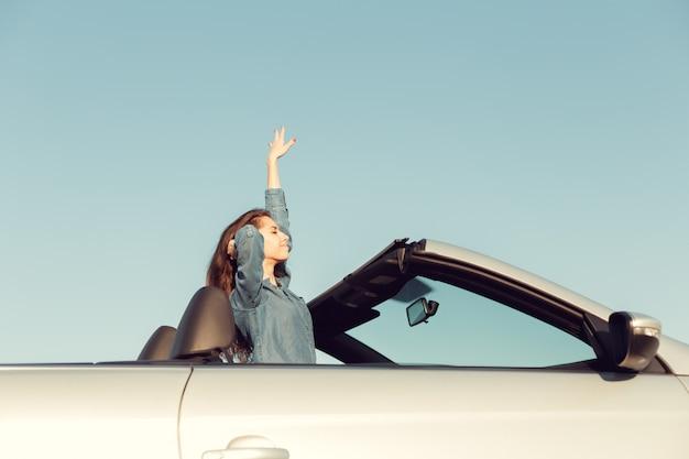 Happy traveler woman in cabrio car
