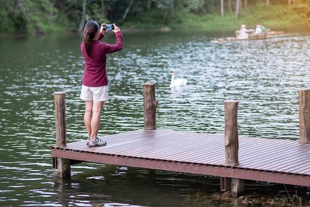 숲 배경으로 호수의 그녀의 스마트 폰으로 사진을 찍는 부두에서 행복 한 여행자 여자