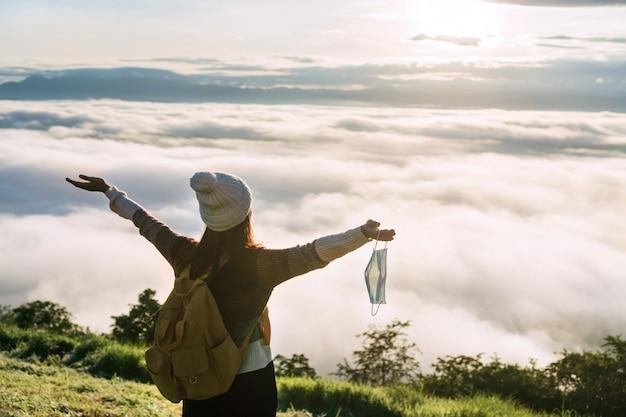 山で手元のサージカルフェイスマスクでリラックスした幸せな旅行者の女性