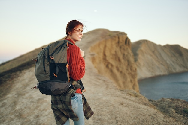 海の近くの山とモデルのバックパックの背面図で休んで幸せな旅行者の女性