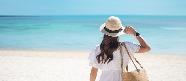 Happy traveler woman in white dress and hat enjoy beautiful sea view