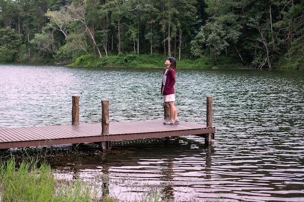 川と森の背景を持つ桟橋に立っている幸せな旅行者のカップル