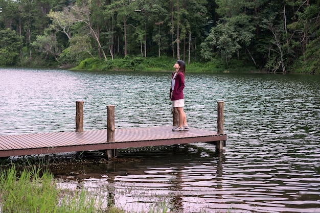 Happy travelers couple standing in a pier with a river and forest background