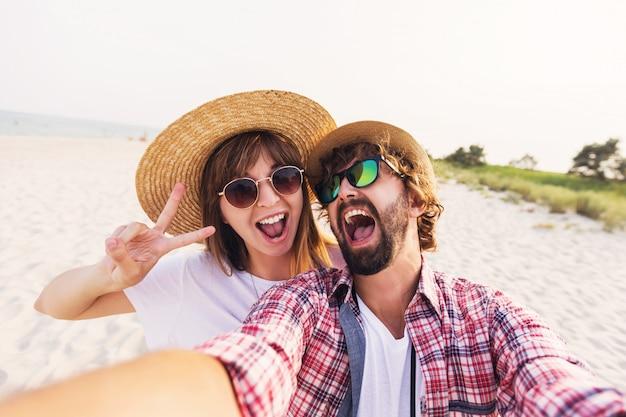 ビーチで電話でselfieを取って愛の幸せな旅行カップル