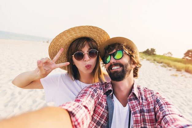 Happy traveling couple in love taking a selfie on phone at the beach