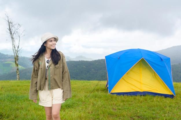 キャンプテントの近くで楽しんでリラックスして幸せな旅行女性