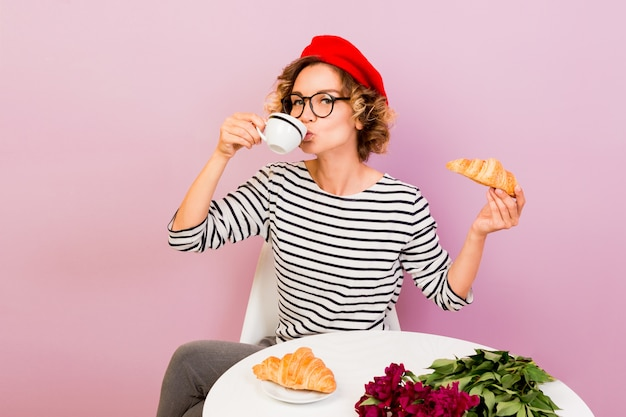 Happy traveling woman in france eating croissans with coffee, sits by the table on pink