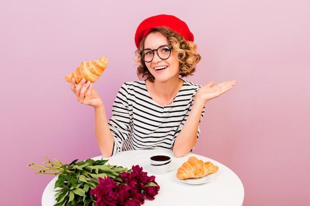 フランスのコーヒーとクロワッサンを食べて幸せな旅行女はピンクのテーブルに座っています。