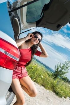 Happy traveling woman sitting in car trunk and resting on stop in rural field. summer lifestyle