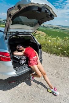 Счастливая путешествующая женщина, сидящая в багажнике автомобиля и отдыхающая на остановке в сельской местности. летний образ жизни