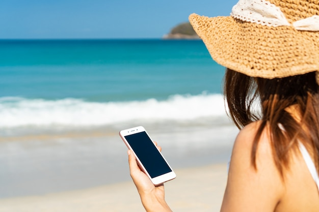 Happy traveller asian woman  enjoys at tropical beach while using smart phone on vacation. summer on beach concept.