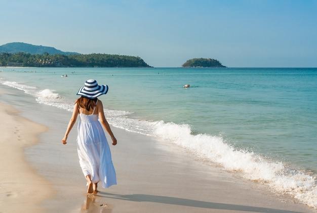 白いドレスを着た幸せな旅行者アジアの女性は、休暇中に熱帯のビーチで楽しんでいます。夏のビーチコンセプト。