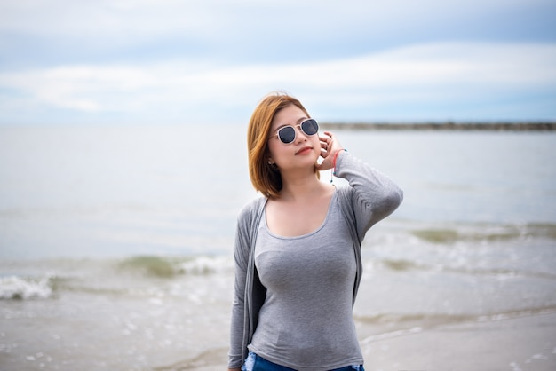 Happy traveller asian woman wearing sunglasses at the beach,enjoying and relaxing time