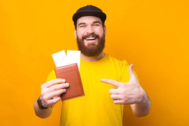 Happy traveller pointing at passport with airplane tickets, lets go travel