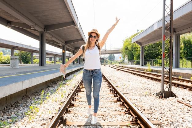 Happy traveller on railroad tracks