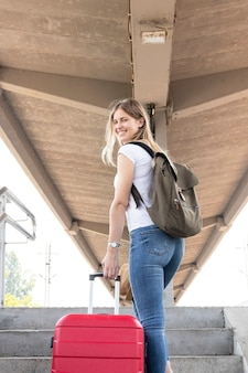 Счастливый путешественник, улыбаясь на вокзале