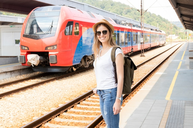 Happy traveller with train in background