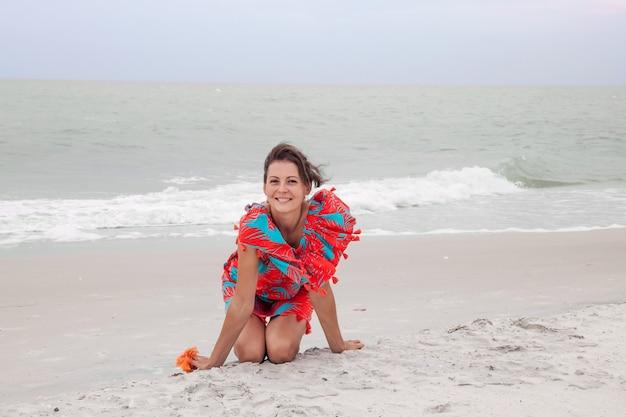 Счастливая женщина путешественника в красивом красочном платье наслаждается пляжными каникулами.