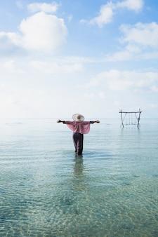 Счастливая путешественница в фиолетовом платье и летней шляпе наслаждается отдыхом на тропическом пляже на острове каримун джава
