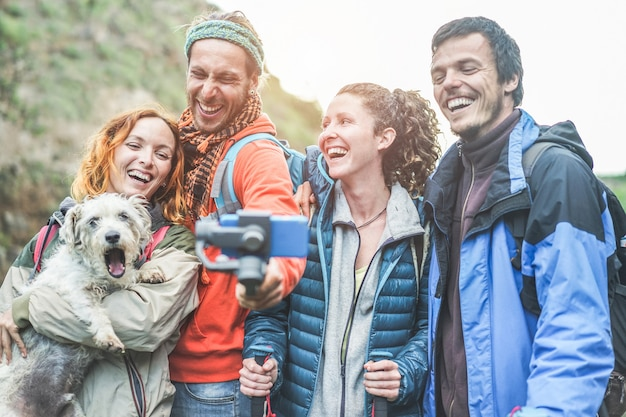 Happy trekkers people making video vlog with gimbal phone - young hiker friends having fun on mountain excursion day - technology trends and sport concept - main focus on center guys faces