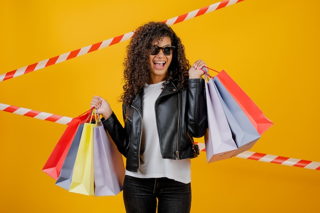 Happy trendy black girl with colorful shopping bags isolated over yellow with signal tape