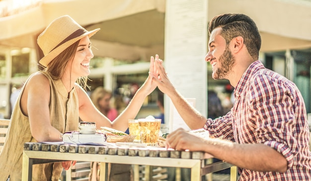 Happy trendy couple having tender moments in bar kiosk restaurant