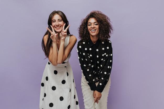 Счастливые модные девушки с прической брюнетки в черно-белой одежде в горошек смотрят в камеру и улыбаются на изолированной стене