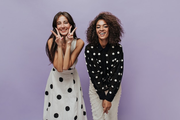 Happy trendy girls with brunette hairstyle in polka dot black and white clothes looking into camera and smiling on isolated wall
