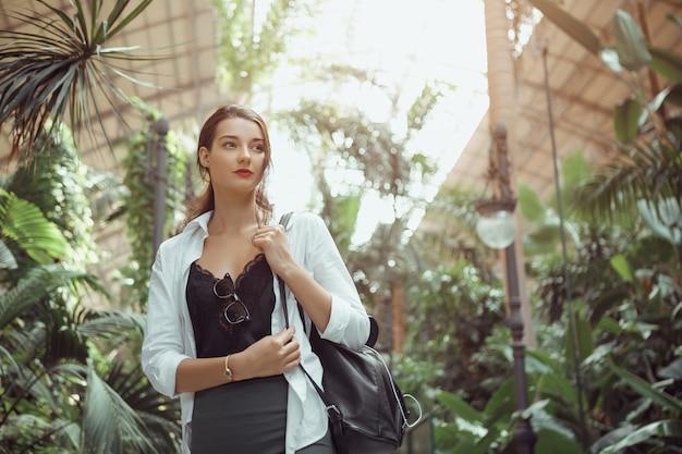 プエルタデアトーチャ電車で立って目をそらしているバックパックを持つ幸せなトレンディな観光客の女性