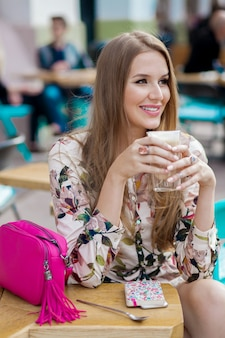 カフェのテーブルに座って幸せなトレンディな若いスタイリッシュな女性