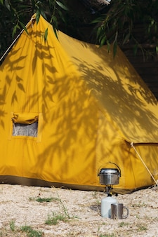幸せな旅-背景にバーナー、ボウラー、カップ、ヴィンテージの黄色いテント