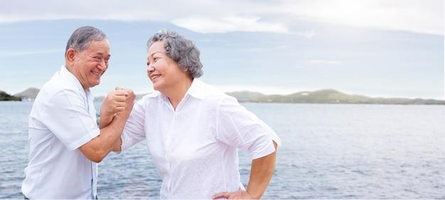 ダンスアクションとオーシャンサイド旅行の概念の健康でシニアアジアの親との幸せな旅行