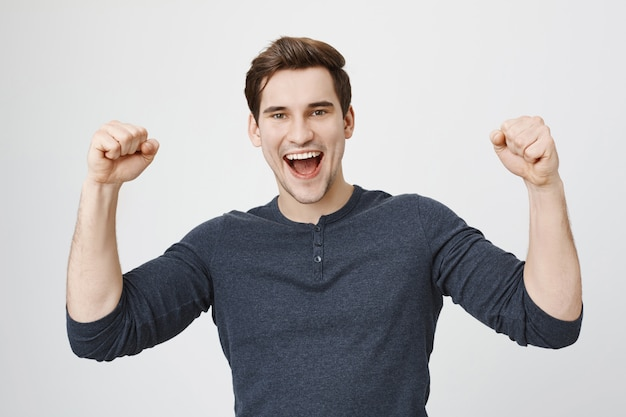 L'uomo trionfante felice raggiunge l'obiettivo, alza le mani e grida di sì
