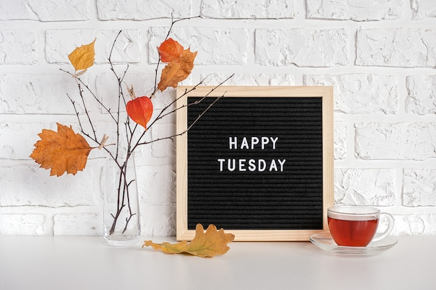 Happy tuesday text on black letter board and bouquet of branches with yellow leaves on clothespins in vase