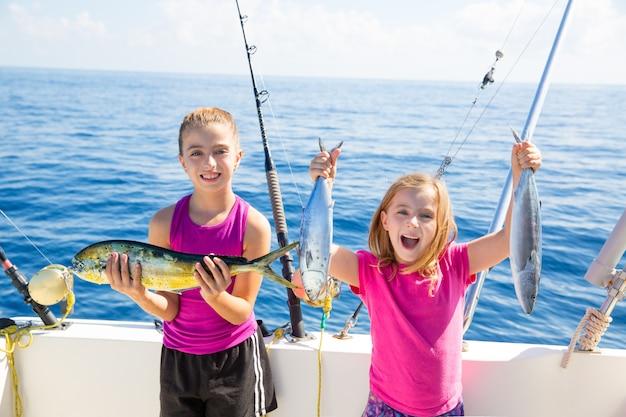 Happy tuna fisherwomen kid girls with fishes catch