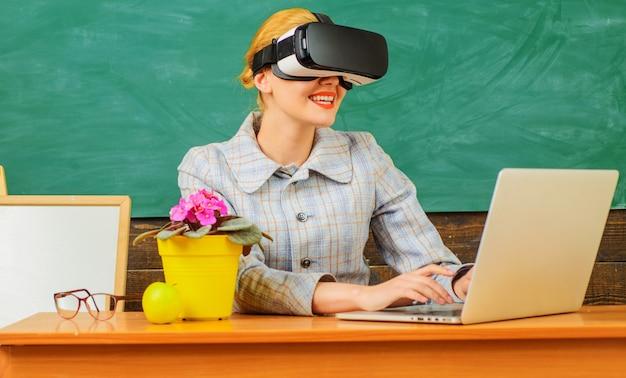 教室で幸せな家庭教師。 vrヘッドセットのラップトップと笑顔の先生。デジタル教育。スマートスクールの最新テクノロジー。 Premium写真