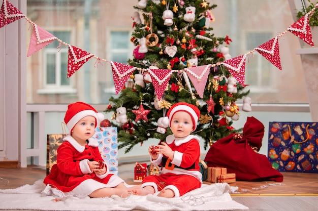 サンタクロースに扮した幸せな双子の赤ちゃんがリビングルームの自宅のクリスマスツリーの近くに座っています
