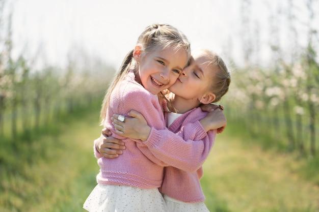 幸せな双子の姉妹は、緑に咲くリンゴの果樹園を背景に抱擁します。片方の妹がもう片方の頬にキスをします。