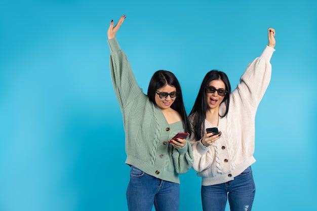 Счастливые сестры-близнецы в 3d-очках со смартфонами на синем фоне