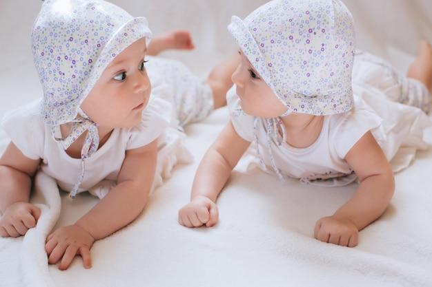 Счастливые близнецы в забавных шапках. дети девочки 7 месяцев.