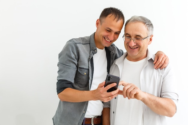 幸せな2世代の男性家族老父は、モバイルアプリを使用して面白いソーシャルメディアビデオを見てスマートフォンのボンディングを使用して楽しんで楽しんでいる若い成長した大人の息子を抱きしめています