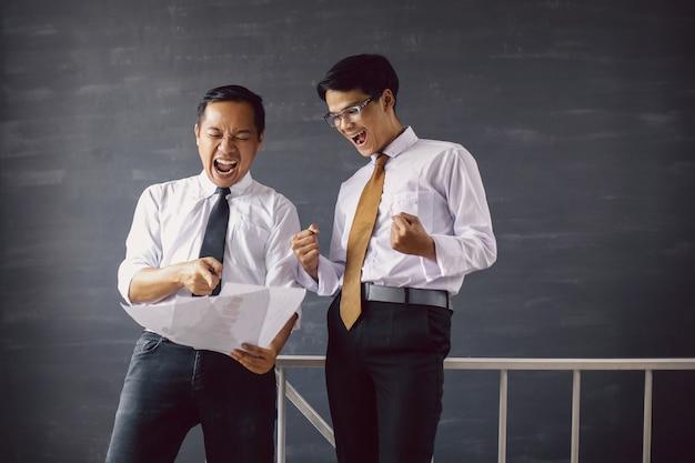 幸せな2人のアジアのビジネスマンは、勝利のジェスチャーでレポートの紙を見てショックを受け、驚いた