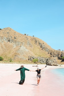 Happy two asian women in summer hat walking together on pink sand beach